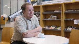 Masse Hellström sitter vid ett kaffebord i Kimito bibliotek