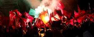 Demonstranter viftar med den turkiska flaggan under en demonstration vid Taksim Square i Istanbul, Turkiet, den 18 juli 2016.