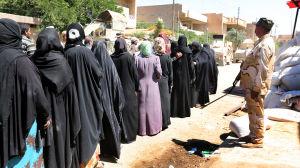 Evakuerade civila nära gamla staden i västra Mosul köar för att få mjöl.