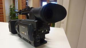 En svart filmkamera på ett bord.