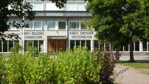 En byggnad skymtar bakom träd och buskar, det är Karis-Billnäs gymnasium.
