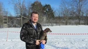 man med hund i famnen i vinterlandskap.