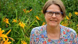 Heidi Hautala på en sommaräng omgiven av gula blommor