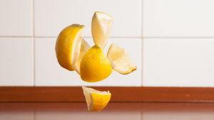 Citronklyftor faller mot ett bord.