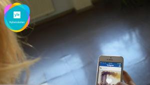 En tjej tittar på Instagram på sin telefon.
