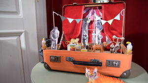Gammal kappsäck står öppen på ett bord föreställande en liten cirkus.