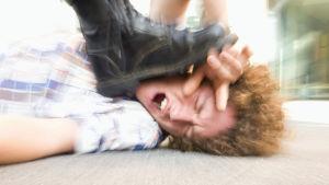 Fot som trycker ner en mans huvud mot golvet.