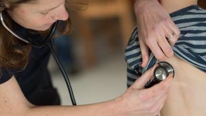 En läkare undersöker ett barn med stetoskop.