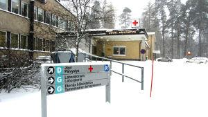 En snöig informationsskylt utanför ett sjukhus i vinterlandskap.