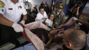 Brandmän räddar en flicka från eldsvåda på ett barnhem i Guatemala den 8 mars 2017. Branden krävde ett tjugotal dödsoffer.