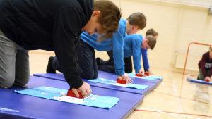 Barn övar på första hjälp på underlag med ett hjärta på.