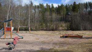 Lekpark med sandlåda, gunga och rutchkana.