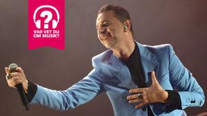 Dave Gahan ler och håller en mikrofon i sin utsträckta högra hand.