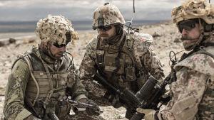 Scen ur danska filmen Kriget där tre soldater sitter på huk i öknen.