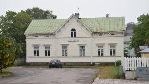 En ljus byggnad i trä med grönt tak. Alan´s café finns i byggnaden i Hangö.
