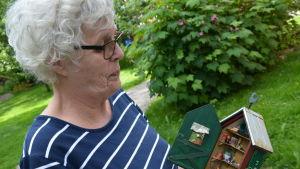 elisabeth westerholm står i trädgården och håller ett tittskåp i händerna. Skåpet är en miniatyrmodell av ett redskapsskåp för en trädgård.