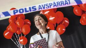 Författaren carina Nunstedt på en scen med röda ballonger i bakgrunden