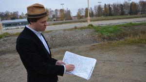 Planläggningsarkitekt Oliver Schulte-Tigges står på travbanan och pekar på en karta över hur bostadsområdet på Travbanan kommer att se ut.