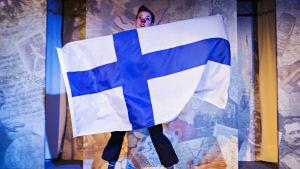 Clownen Tove Qvickström håller i flaggen i pjäsen Finlands historia - en clownföreställning.