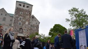 Människor minglar framför försäljningsstånd under businessfestivalen The Shift, Åbo slott i bakgrunden.