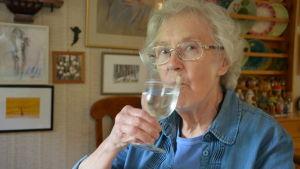 Märta Sjöblom dricker ett glas vatten.