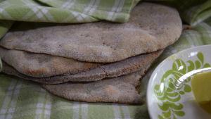Nygräddad tunnbröd under en handduk.