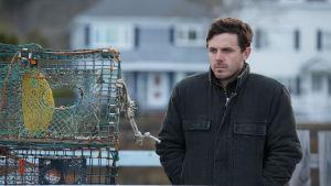 Lee (Casey Affleck) står på en brygga och ser sorgsen ut.