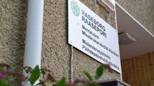 Skylt där det står Raseborg och stads vapen. Under den står det mentalvård, missbrukarbvård/a-kliniken. Skylten sitter på ett hus brevid ingången.