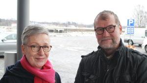 Kati Kytölä med en rosa halsduk runt halsen står bredvid sin make Tarmo Kytölä i Kristinestad.