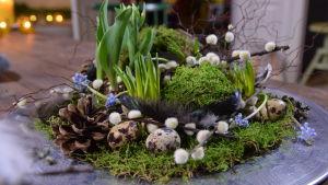 Påsk arrangemang med blommor och mossa på ett fat.