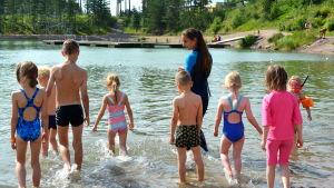 Barn i simskolan går ut i vattnet i Kokon simgrop.
