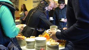 Mänskor tar för sig av kaffe och bakverk.