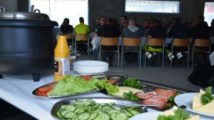 Mat i förgrunden och byggarbetare på taklagsfest i bakgrunden.