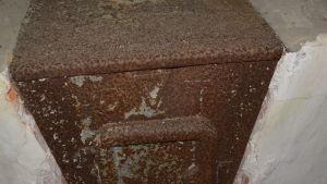 Kamin i bastubyggnad på Tulludden. Tecknet står för Organisation Todt, d.v.s. Fritz Todts arbetsorganisation för tyska riket. Wolksvagen var tillverkare.