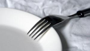 En gaffel på en tallrik på en vit duk.