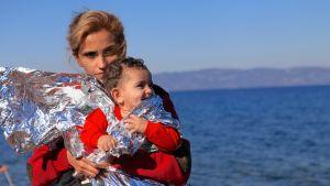 Nainen lapsi sylissään veneessä