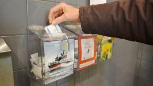 En hand lägger i ett kvitto i en låda.