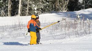 Två pojkar åker upp med skidliften vid Bötombergen i Lappfjärd.