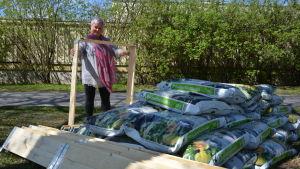 Mari Helin står vid säckar av muld och en blivande odlingslåda.