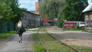 Övergiven tågbana, människor promenerar intill den.