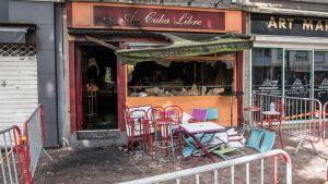 Den brandförstörda baren Au Cuba Libre i Rouen, Frankrike: krossade fönster, sotig utsida och fällda stolar.