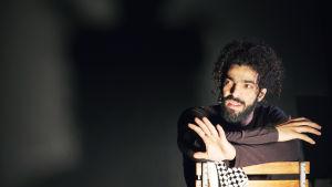 Ramy Essam sitter ner på en stol under föreställningen