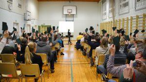 Alla närvarande på invånarmöte om skolornas framtid i östra Borgå viftar med gröna lappar.