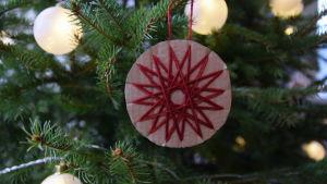 En juldekoration av paff och garn hänger i julgran.