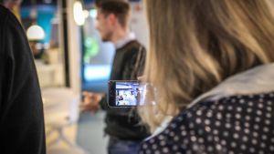 Toimistoympäristö, nainen kuvaa mieshenkilöä, kuva on tarkennettu älypuhelimen ruutuun