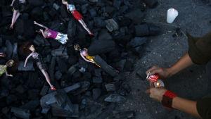 En person tänder ett ljud för offren som dog i eldsvådan.