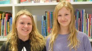 Två unga flickor framför en bokhylla med barnböcker