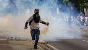 I förgrunden springer en demonstrant med ett rykande föremål i sin hand och skydd för munnen. I bakgrunden fler demonstranter.