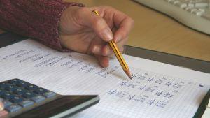 Hand med penna över pappersark med matematikuppgift. Miniräknare.