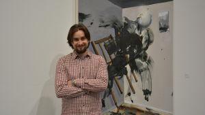 Viljam Heinonen framför sitt konstverk.